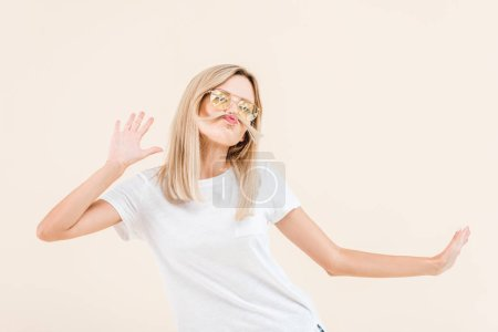young blonde woman in sunglasses having fun with hair isolated on beige