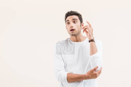 Photo for Surprised young man with open mouth looking away isolated on beige - Royalty Free Image