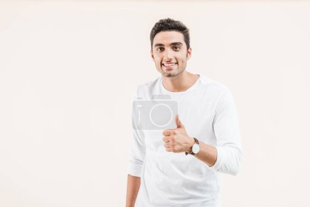 Photo pour Heureux jeune homme montrant pouce levé et souriant à la caméra isolé sur beige - image libre de droit