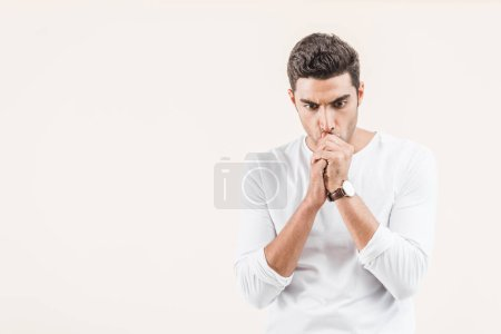 Photo for Focused young man thinking and looking down isolated on beige - Royalty Free Image