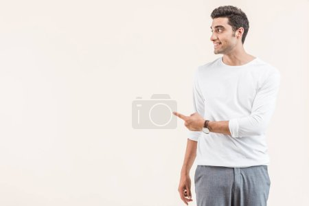 smiling young man looking away and pointing with finger at copy space isolated on beige