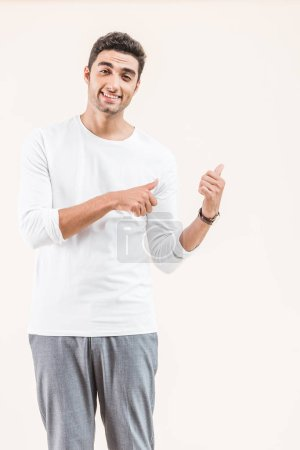 handsome young man pointing at copy space and smiling at camera isolated on beige