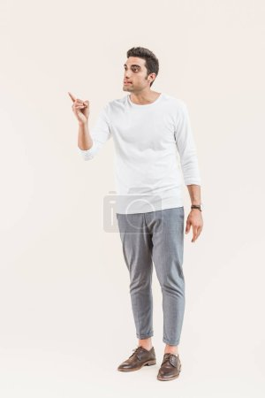 handsome young man looking away and pointing with finger isolated on beige