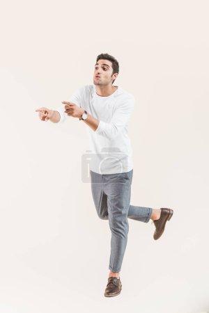 Voir toute la longueur du beau jeune homme à la recherche de loin et en pointant avec doigts isolé sur beige