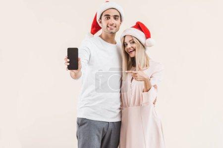 Foto de Feliz pareja joven con sombreros de santa celebración de smartphone con pantalla en blanco y sonriendo a cámara aislada en beige - Imagen libre de derechos
