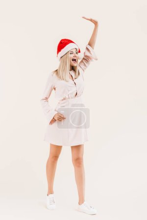 full length view of beautiful happy young woman in dress and santa hat waving hand and looking away isolated on beige