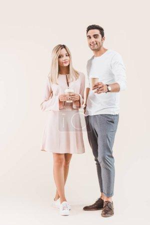 Photo pour Jeune couple tenant des tasses en papier et souriant à la caméra isolé sur beige - image libre de droit
