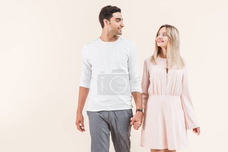 happy young couple holding hands and smiling each other isolated on beige