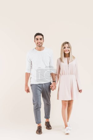 Photo for Happy young couple holding hands and smiling at camera isolated on beige - Royalty Free Image