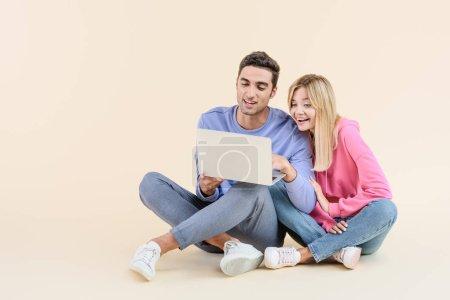 Photo pour Heureux jeune couple assis ensemble et à l'aide d'ordinateur portable isolé sur beige - image libre de droit