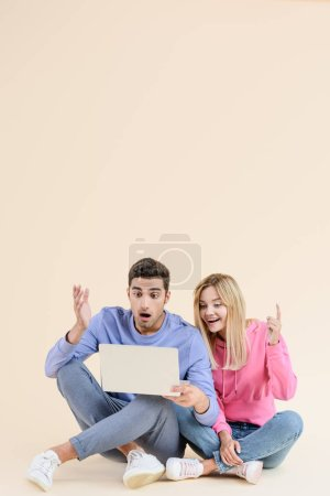 Photo for Surprised young couple sitting together and using laptop isolated on beige - Royalty Free Image