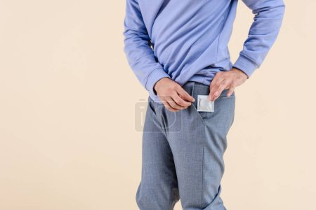 cropped shot of man putting condom into pocket isolated on beige