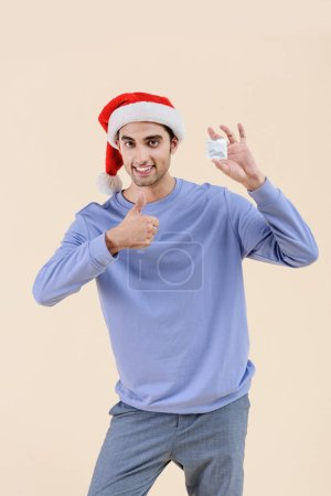 happy young man in santa hat holding condom and showing thumb up isolated on beige