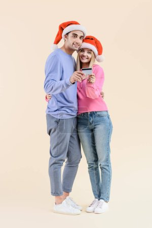 happy young couple in santa hats holding credit card and smiling at camera isolated on beige
