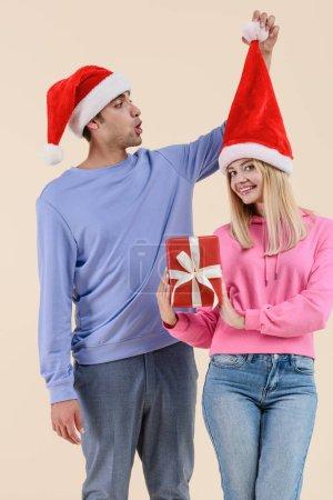 heureuse jeune femme tenant Noël présent et souriant à la caméra tout homme s'amusant avec Bonnet de Noel isolé sur beige