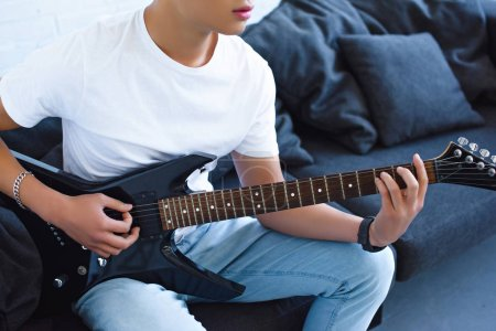Photo for Cropped image of guitarist playing electric guitar at home - Royalty Free Image