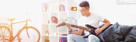 Photo pour Vue panoramique de bel homme asiatique gaucher Guitare électrique sur canapé à la maison - image libre de droit