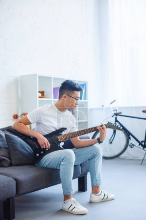 handsome asian man playing F major chord on unplugged electric guitar at home