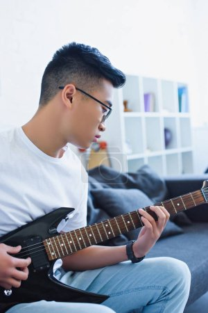 handsome asian man playing electric guitar at home