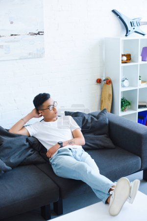 Photo for High angle view of pensive handsome asian man sitting on sofa with legs on table at home, looking away - Royalty Free Image
