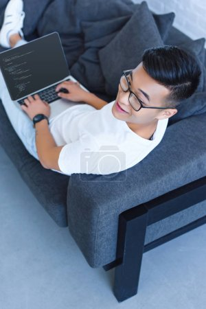 Photo pour Vue d'angle élevé de bel homme asiatique allongée sur le canapé et à l'aide de portable avec le code html à la maison - image libre de droit