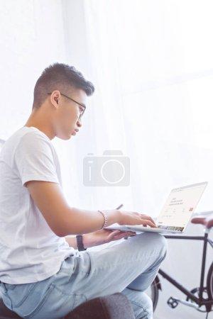 Photo pour Vue latérale du bel homme asiatique avec ordinateur portable chargé airbnb page sur canapé à la maison - image libre de droit
