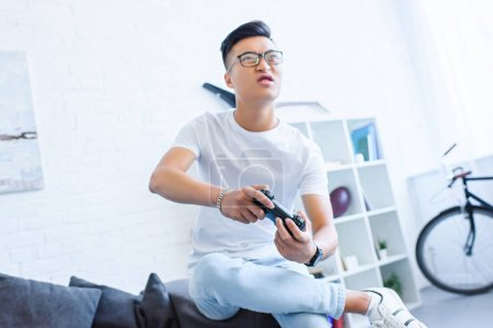 irritated asian man playing video game with joystick on sofa at home