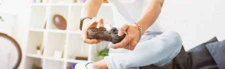 cropped image of man playing video game on sofa and holding gamepad at home