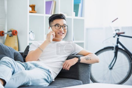 smiling handsome asian man lying on sofa and talking by smartphone at home