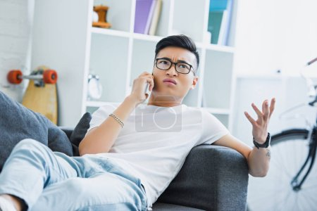irritated asian man lying on sofa, talking by smartphone and gesturing at home