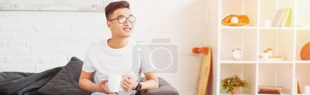 panoramic view of smiling handsome asian man sitting on sofa with cup of tea and looking away in living room