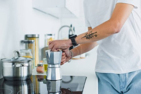 close-up partial view of young tattooed man making coffee in kitchen