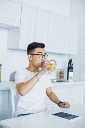 young asian man in eyeglasses drinking juice and looking away in kitchen