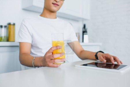 Schnappschuss von jungem Mann mit Saftglas und digitalem Tablet