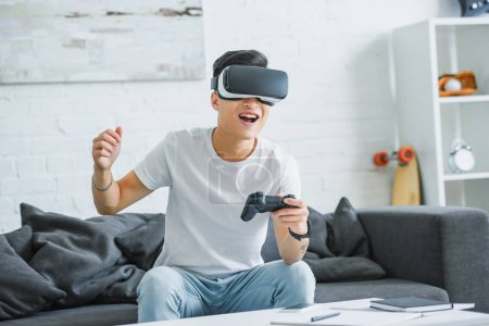 Photo for Happy young man in virtual reality headset playing with joystick at home - Royalty Free Image