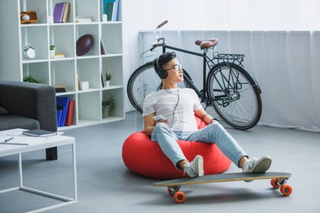 young asian man in headphones sitting in bean bag chair and using smartphone at home