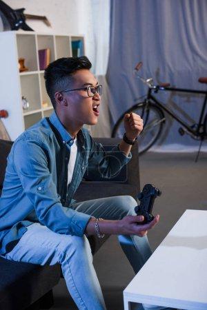 Photo pour Excité jeune asiatique homme jouer jeu vidéo avec joystick et gagner à la maison - image libre de droit