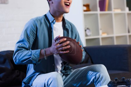 cropped shot of smiling young man holding rugby ball and watching sport match at home