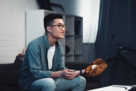 smiling young asian man with baseball glove and ball sitting on couch and watching sport match at home