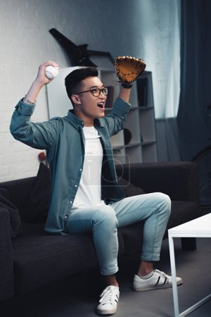 excited young man with baseball glove and ball sitting on couch and watching sport match at home
