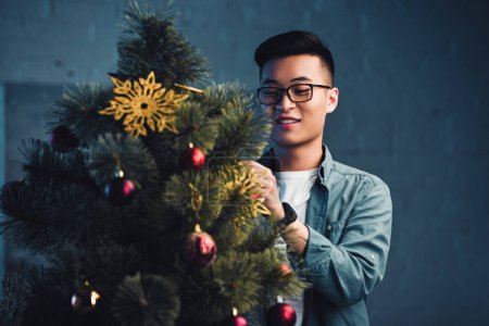 smiling young asian man in eyeglasses decorating christmas tree at home
