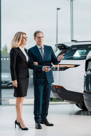 smiling businessman and businesswoman choosing new automobile in showroom