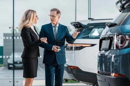 businessman and businesswoman choosing new automobile in showroom