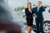 pensive businessman and businesswoman choosing new automobile in showroom