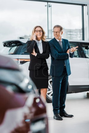 businessman talking on smartphone while businessman choosing new automobile in showroom