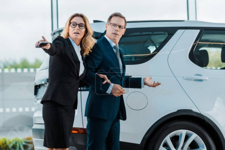 businessman and businesswoman pointing away while choosing new automobile in showroom