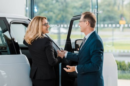 smiling businessman helping businesswoman to sit into new car in showroom