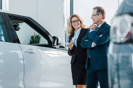 smiling business couple looking for new automobile in dealership salon
