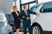 business couple looking for new automobile in dealership salon