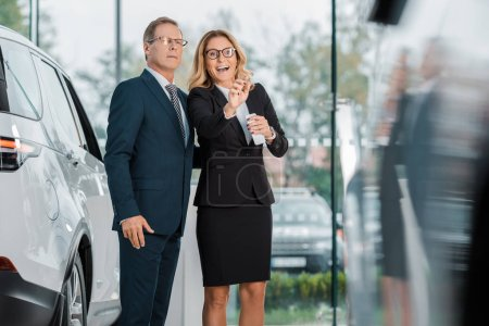 Photo for Businesswoman with smartphone pointing away while looking for new automobile together with businessman in dealership salon - Royalty Free Image